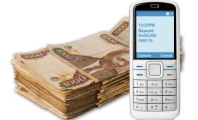 A phone beside a stack of cash in Kenyan currency